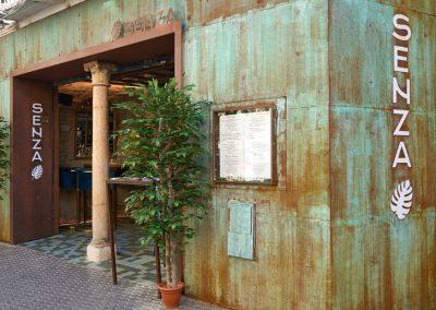 SENZA, una nueva propuesta gastronómica en el centro de Sevilla. De la mano de los promotores de Burro Canaglia, abre SENZA. Una propuesta gastronómica basada en la cocina italiana, con un enfoque canalla y atrevido, y de una amplia carta de coctelería en un ambiente atractivo y con un llamativo diseño.La carta incorpora ingredientes como la trufa, el caviar de aceite de oliva, quesos artesanos locales, el plancton marino, o elaboraciones de vanguardia, como el uso de hielo seco, nitrógeno líquido, ahumados…. También cuentan con horno de brasas Josper para sus carnes y pescados. Como platos estrella, destacamos el steak tartar de vaca rubia gallega con salsa cipriani, el carpaccio de presa ibérica de bellota con marinada de palo cortado, el risotto de setas y carrilleras de ibérico al horno de brasas o su pizza de Bogavante. También el raviolacci relleno de puntas de espárragos y almendras con crema de mandorle, panceta italiana y foie fresco, o el solomillo de atún rojo salvaje a las brasas sobre ajoblanco de tinta de calamar.En cuanto a la distribución del espacio, podemos distinguir dos ambientes diferenciados: por un lado la zona de barra y mesas altas, con un enfoque más informal en la que se puede disfrutar de la carta, y por otro lado, la zona de comedor, con espacio para 50 comensales, y con un diseño fresco y acogedor.La decoración conjuga varios estilos, principalmente industrial y colonial, e incorporando elementos recuperados típicos de la arquitectura regional andaluza.