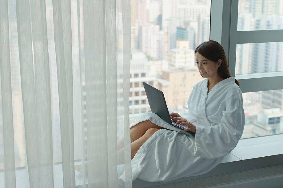 mujer trabajando con portátil en un hotel con vistas